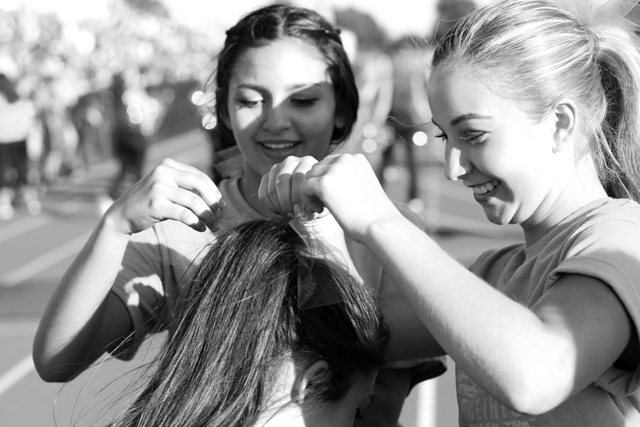 Cheerleaders Brenna Bradley and Mia LeClaire tie a ribbon in their teammate's hair