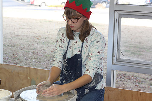 Mary Rongish plays the role of Christmas Elf as she works the pottery wheel.