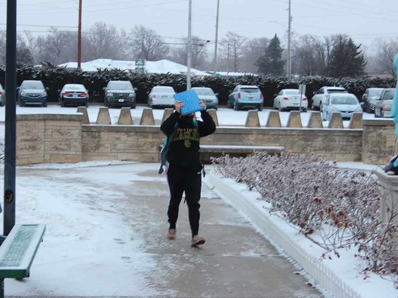A student uses a notebook for protection from the winter weather. Photo by Gavin Bush.